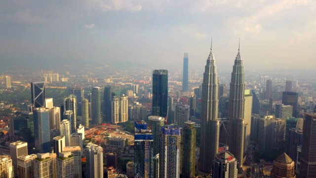 flyg foto över kuala lumpur downtown, malaysia. finans distrikt och affärs centra i smart urban stad i asien. sky skrapa och höghus vid solnedgången. - petronas twin towers bildbanksvideor och videomaterial från bakom kulisserna
