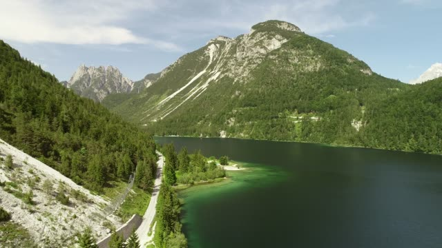 aerial view of lake with green water near the cave del predil, itally. - lombardia video stock e b–roll