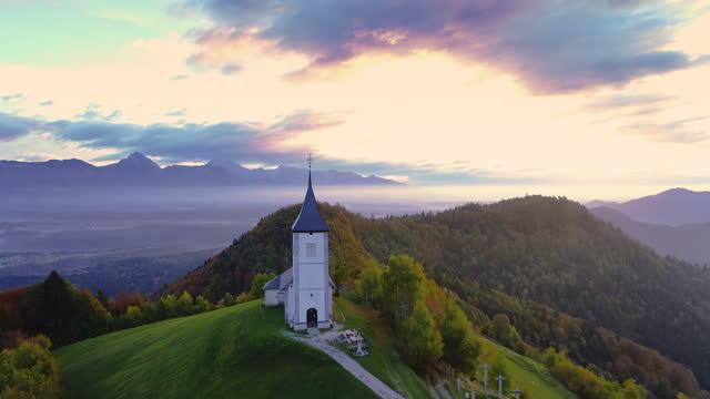 vídeos de stock, filmes e b-roll de vista aérea da paisagem da igreja de st. primoz perto de jamnik, eslovênia e alpes julianos ao fundo - eslovênia
