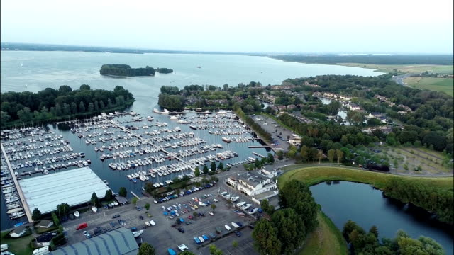 veduta aerea della barca dock con grande lago in background - molla video stock e b–roll