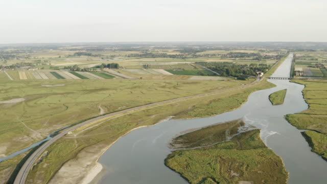 灰色の曇り空に対する農業場に囲まれた大きな川の空中写真。アクション。農村風景の空中写真 ビデオ