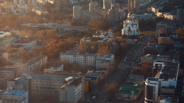 Aerial view of large russian city, buildings, trees, roads with moving cars and church in summer sunny morning. Stock footage. Beautiful urban landscape