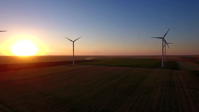 Aerial view of large wind turbines in a wind farm at sunset video