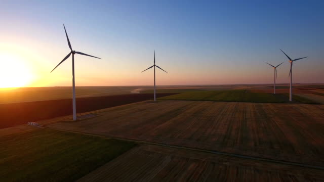 Aerial view of large wind turbines in a wind farm at sunset Aerial view of large wind turbines in a wind farm at sunset, producing sustainable and renewable energy. windmill stock videos & royalty-free footage