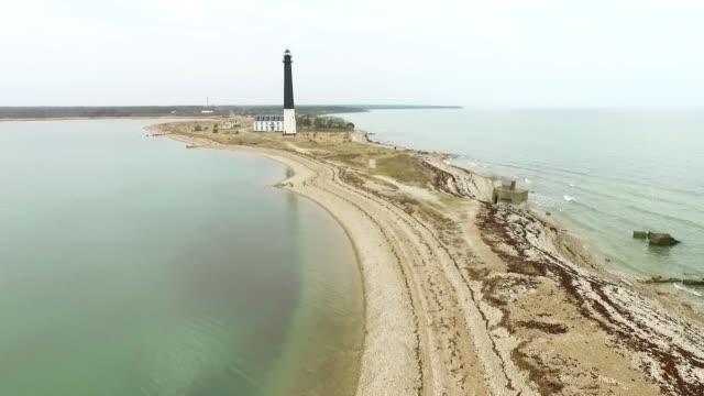vídeos de stock, filmes e b-roll de vista aérea do farol na península de sorve, ilha de saaremaa em estónia. - países bálticos