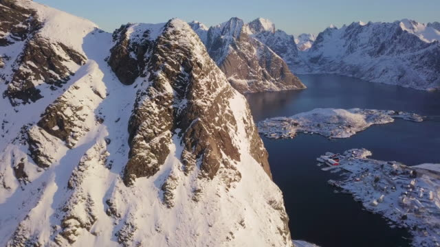 vídeos de stock e filmes b-roll de aerial view of lofoten winter scenery with village of reine at sunrise, norway - fiorde