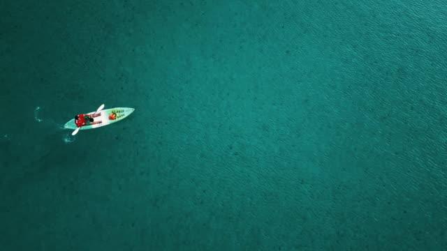 vídeos de stock, filmes e b-roll de vista aérea da canoa solitária no mar na tailândia. - caiaque