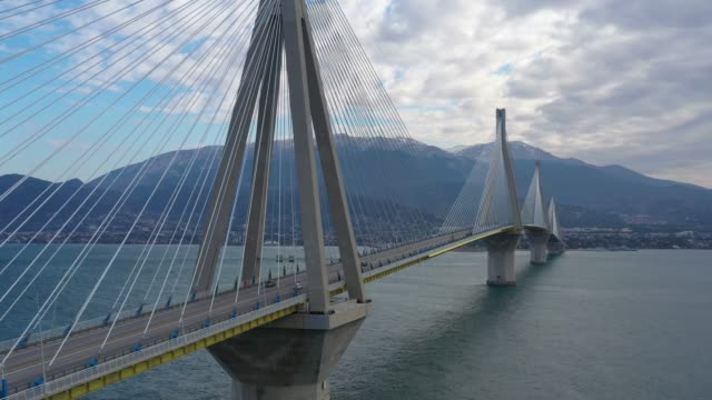 Aerial view of long cable-stayed Rio bridge in Greece at clouds weather, Ferry station Aerial view of long cable-stayed Rio bridge in Greece at clouds weather suspension bridge stock videos & royalty-free footage