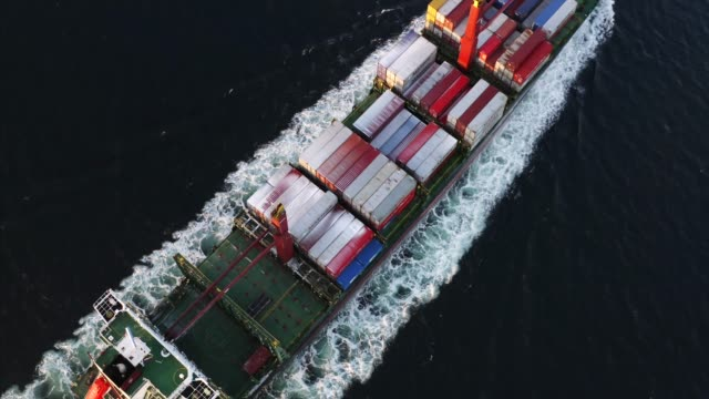 aerial view of long massive cargo ship with containers sailing in the ocean - chiatta video stock e b–roll
