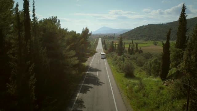 Aerial view of long straight road with bus in the countryside in Greece.