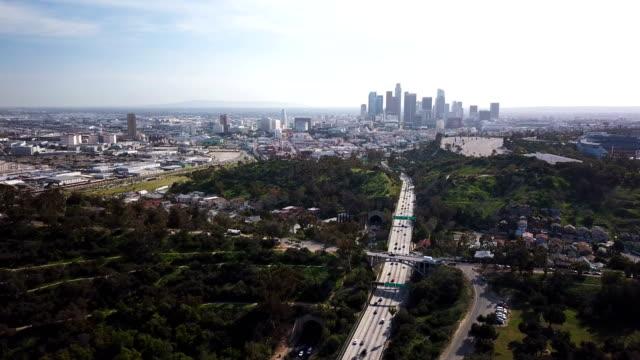 4k flygfoto över los angeles freeway och skyline med trafik och tunnlar - hollywood sign bildbanksvideor och videomaterial från bakom kulisserna