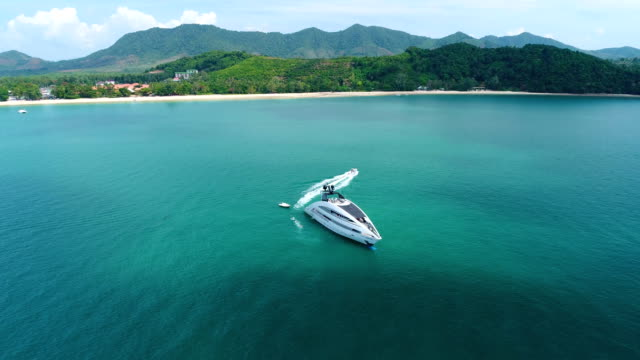 Aerial view of luxury yacht in the sea near the beach. Aerial view of luxury yacht in the sea near the beach. Small boat going out from the big sheep. Thailand. military private stock videos & royalty-free footage