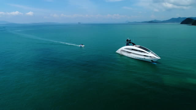 Aerial view of luxury yacht in the sea. Aerial view of luxury yacht in the sea. Small boat coming to big ship. Thailand. yacht stock videos & royalty-free footage