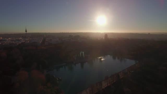 vídeos de stock, filmes e b-roll de vista aérea de madrid no alvorecer, spain cena da cidade com parque de buen retiro - sol nascente horizonte drone cidade