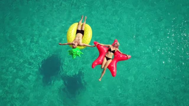 vídeos de stock, filmes e b-roll de vista aérea de homem e mulher flutuando sobre colchões infláveis tocar nos pés. - inflável
