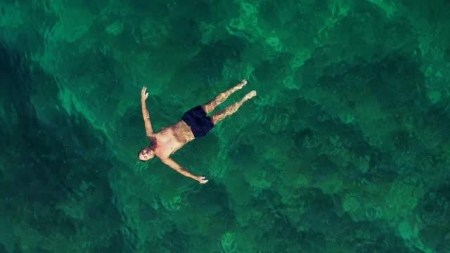 海に浮かぶ男の空撮。 - 水に浮かぶ点の映像素材/bロール