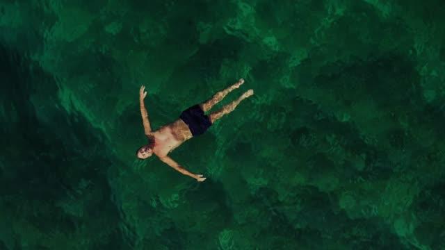 vídeos de stock, filmes e b-roll de vista aérea do homem flutuando de costas no mar. - flutuando na água