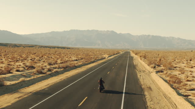 Aerial view of man riding motorcycle down desert road at sunset