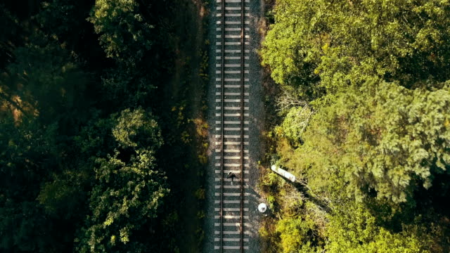 Aerial view of man running up on train track. Vertical drone view. Concept of chasing dreams and surviving life trials video