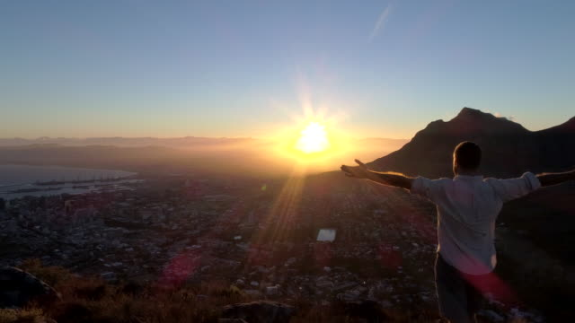 Aerial view of man welcoming the sun Aerial view of a young man reaching the top of Lion's head mountain in Cape Town, South Africa. western cape province stock videos & royalty-free footage
