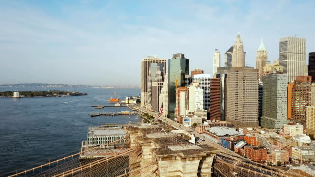 Aerial view of Manhattan in New York, America. Drone flying over the East river, Brooklyn bridge and waving on wind flag video