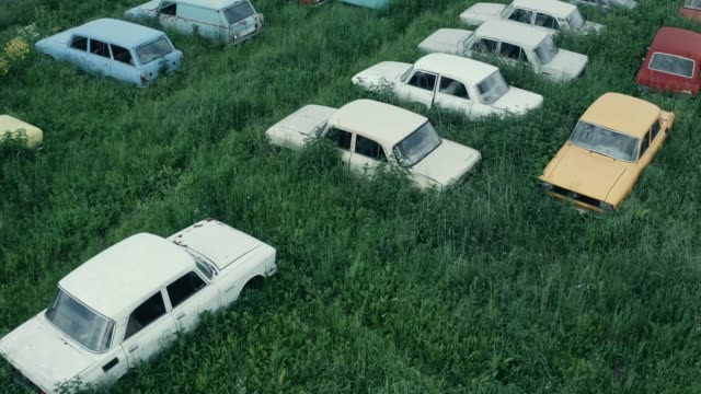 Aerial view of many abandoned rusty vintage cars in green grass, retro autos cemetery