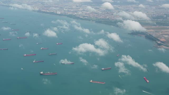 vídeos y material grabado en eventos de stock de 4k vista aérea de muchos buques portacontenedores anclados en el área de agua contra terminales portuarias - anclado