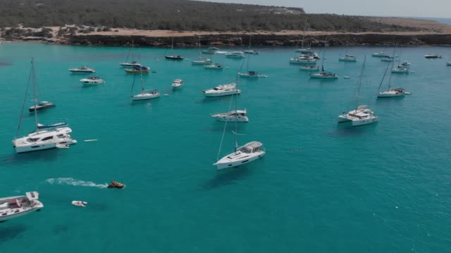 Aerial View of many yachts in a bay on Formentera island. Cala Saona bay drone footage. Yachting in the Balearic islands