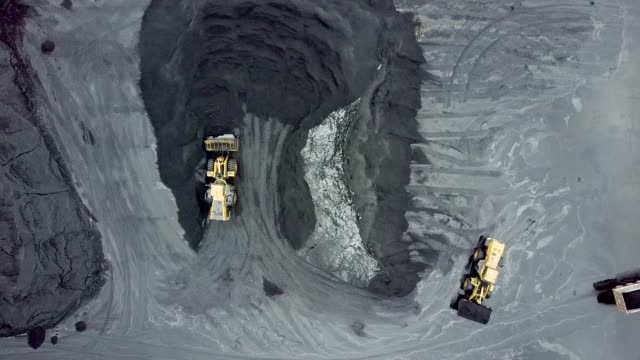 aerial view of mechanical digger and truck in coal mining area - ископаемое топливо стоковые видео и кадры b-roll