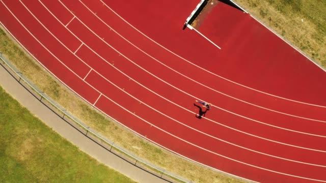 pistetrafında koşan orta yetişkin kadın atletin havadan görünümü - uzun adımlarla yürümek stok videoları ve detay görüntü çekimi