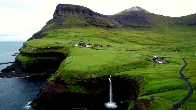 Video Aerial view of Múlafossur waterfall near a small village, Faroe island.