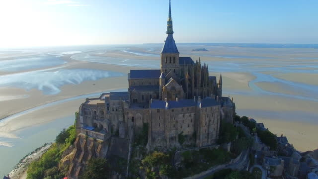aerial view of mont saint michel, iconic island and monastery protected by unesco at twilight, normandy, france, 4k uhd - замок строение стоковые видео и кадры b-roll