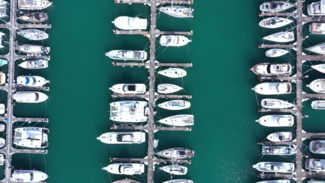 vídeos de stock, filmes e b-roll de vista aérea de barcos atracados no porto - marina
