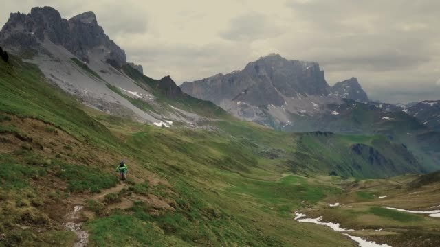 aerial view of mountain biker on narrow trail in alps - andare in mountain bike video stock e b–roll