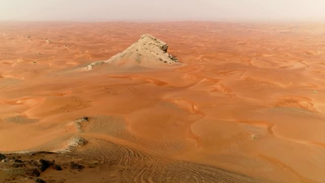 aerial view of mountain in the middle of desert during sunset, u.a.e - abu dhabi стоковые видео и кадры b-roll