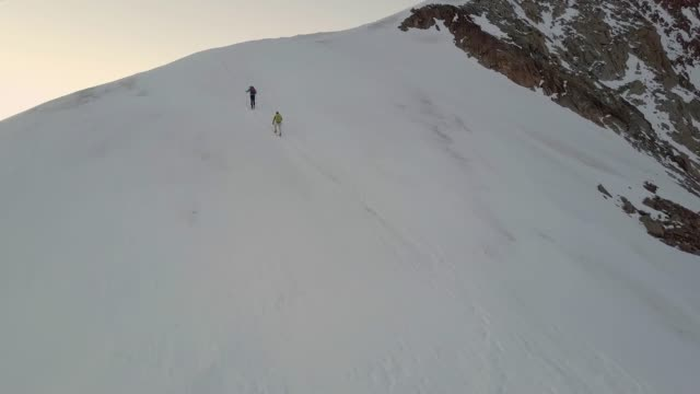 Aerial view of mountaineers reaching summit of mountain at sunrise They approach summit, at sunset mountain peak stock videos & royalty-free footage