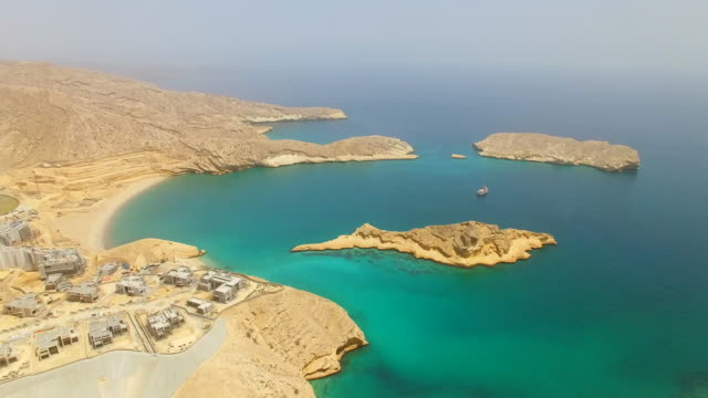 aerial view of muscat bay, dive resort, turquoise crystal clear water of indian ocean, beaches, blue lagoons and small islands, oman, arabian peninsula, 4k uhd - oman filmów i materiałów b-roll