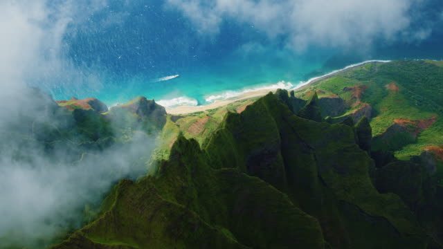 Aerial View of Napali Coast Cinematic aerial view of dramatic mountains and ocean on Napali Coast, Kauai, Hawaii hawaii islands stock videos & royalty-free footage