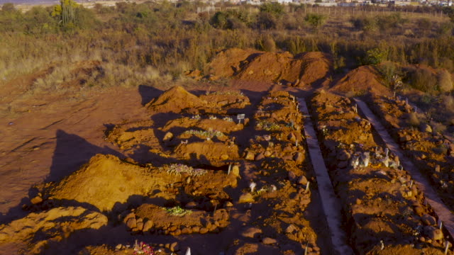 aerial view of new graves at a cemetery in the time of coronavirus covid-19 pandemic in south africa - cadavere video stock e b–roll