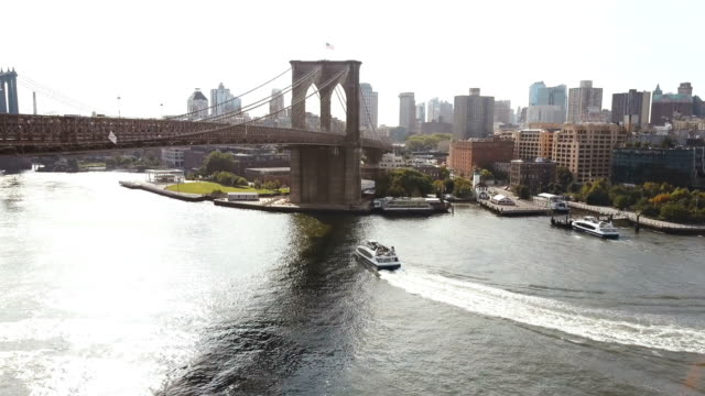 Aerial view of New York, America. Drone flying over the East river, boat riding through the water, under Brooklyn bridge video