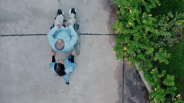 自宅で先輩と車椅子を押す看護師の空中写真。 - 老人ホーム点の映像素材/bロール