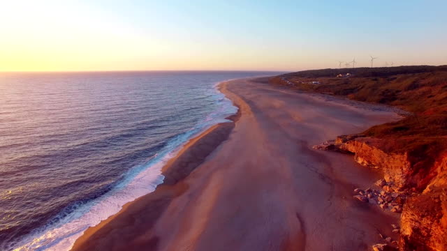 Aerial view of ocean, north Beach and Nazare lighthouse at sunset, Portugal video