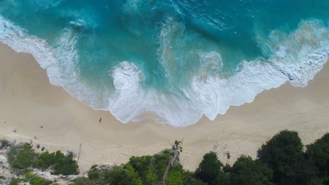 aerial view of ocean waves crashing on beach by 4k drone footage. - индонезия стоковые видео и кадры b-roll