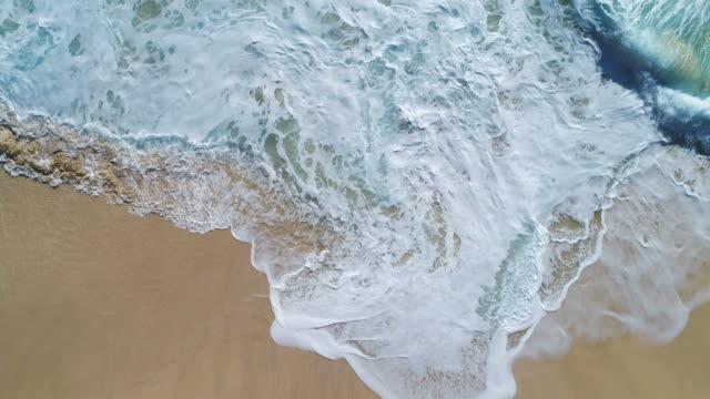 vídeos y material grabado en eventos de stock de vista aérea de las olas del océano rompiendo en la playa por imágenes de drone de 4k. - marea