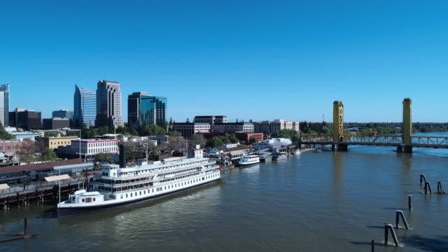 Aerial view of Old Sacramento Waterfront District, with the remote view of Tower Bridge and Sacramento Downtown business districtin the backdrop. Drone video with the complex forward and panoramic camera motion.