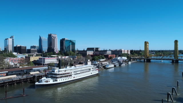 Aerial view of Old Sacramento Waterfront District, with the remote view of Tower Bridge and Sacramento Downtown business districtin the backdrop. Drone video with the forward camera motion.