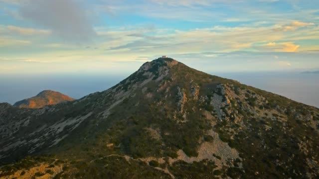 vídeos de stock, filmes e b-roll de vista aérea de oros montanha na ilha de aegina, grécia em belo pôr do sol com céu dramático. - ática ática