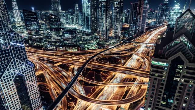 vidéos et rushes de vue aérienne t/l du viaduc, du métro et du trafic urbain la nuit / dubaï, émirats arabes unis - route surélevée