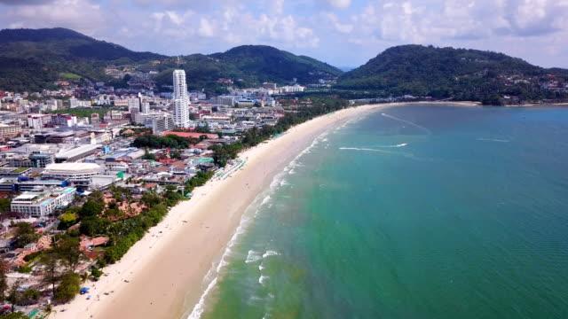 vídeos de stock, filmes e b-roll de vista aérea da praia de patong, do console e do mar de phuket no verão, e da cidade urbana com o céu azul para o fundo do curso, oceano de andaman, tailândia. - phuket