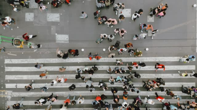 vídeos de stock e filmes b-roll de aerial view of pedestrians walking across with crowded traffic. - pessoa